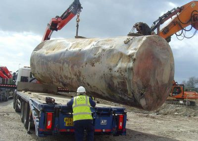 Tank being loaded onto transport for disposal off-site